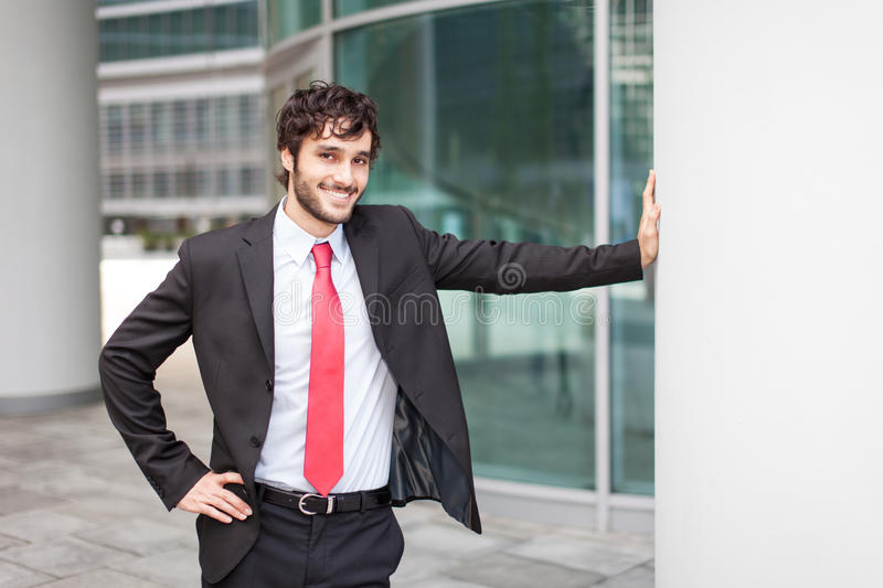 Businessman leaning on a metal column. Smiling handsome businessman leaning on a metal column royalty free stock image