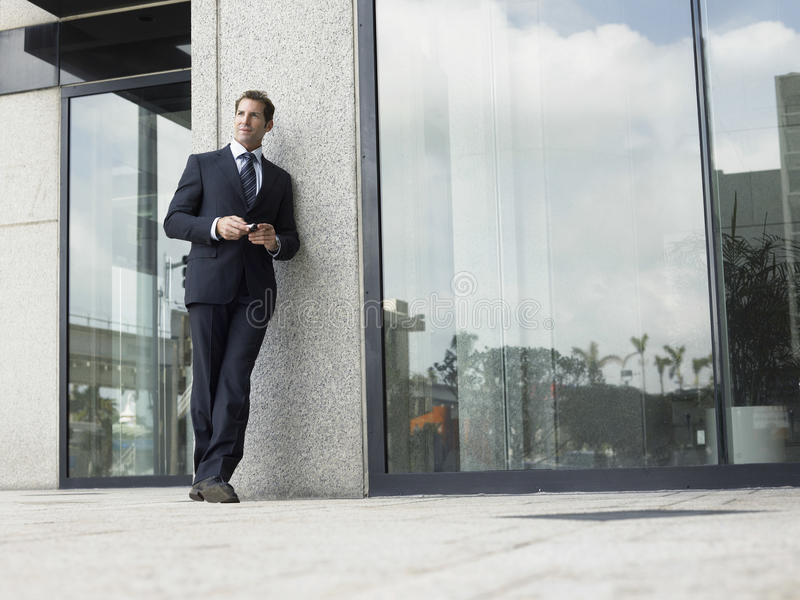 Businessman Leaning On Office Wall While Looking Away royalty free stock photos