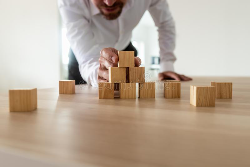 Businessman leaning in to carefully assemble pyramid shape with. Blank wooden blocks on office desk. Conceptual of business start up and vision stock photo
