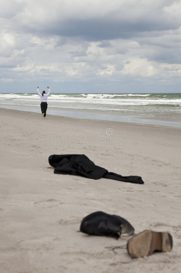 Businessman Leaving Clothes On Beach Running Away royalty free stock photo