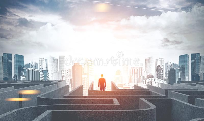 Businessman leaving a maze going to city, dawn. Businessman figure leaving a gray maze and going into a city at dawn. Concept of hope and solution search in stock images