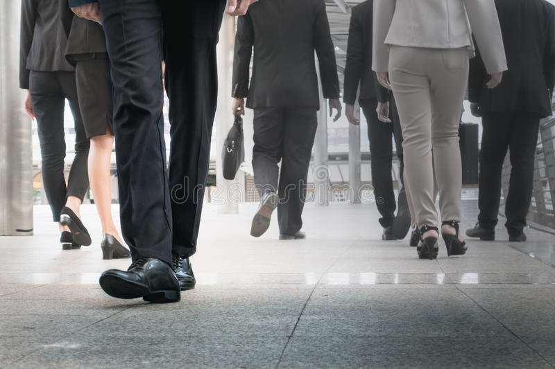 Businessman legs walking go forward as outstanding by other legs. Walking as opposite direction on business street stock images