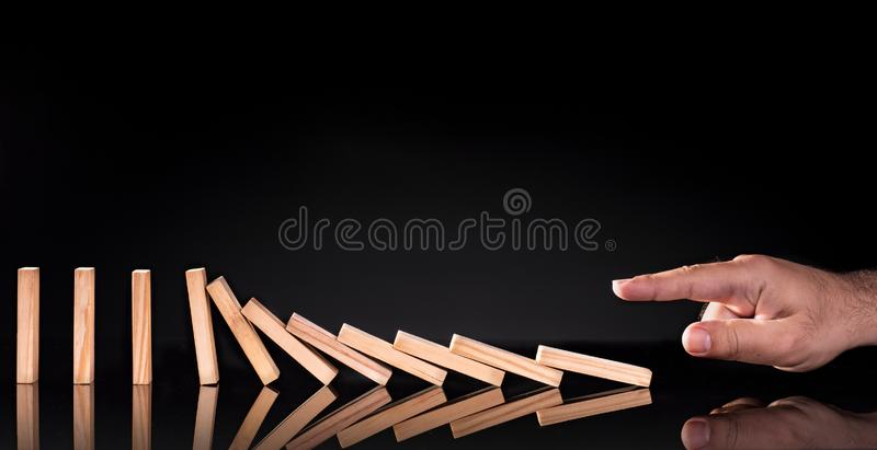 Businessman Letting Dominoes Chain Toppling stock images