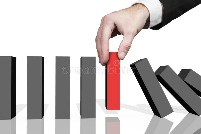 Businessman lifting red domino block royalty free stock photo