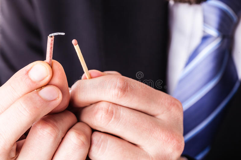 Businessman lighting a tiny firecracker. A young and handsome businessman with a tiny red firecracker royalty free stock images