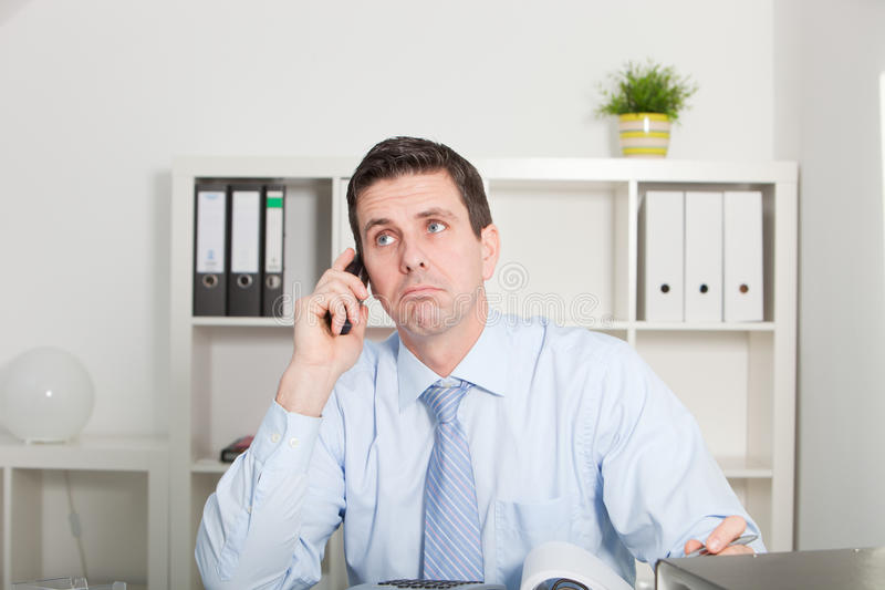 Businessman listening to his mobile stock photography