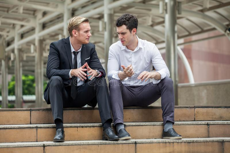 businessman listening to partner talking sitting on steps in city outdoors . team discussing.consulting client.meeting,sharing his stock images