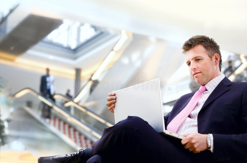 Businessman in lobby. Well dressed businessman sitting in the lobby and using laptop computer