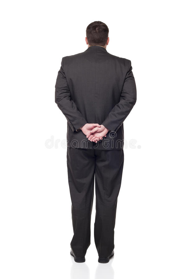 Businessman looking away from camera. Isolated full length studio shot of the back side of a businessman facing away from the camera with his hands clasped stock image