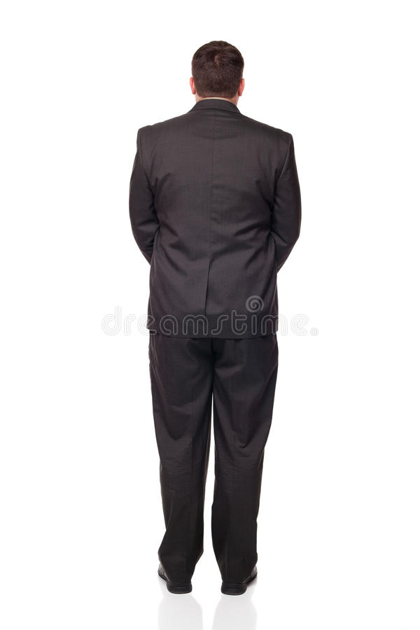 Businessman looking away from camera. Isolated full length studio shot of the back side of a businessman facing away from the camera with his hands clasped in royalty free stock photos