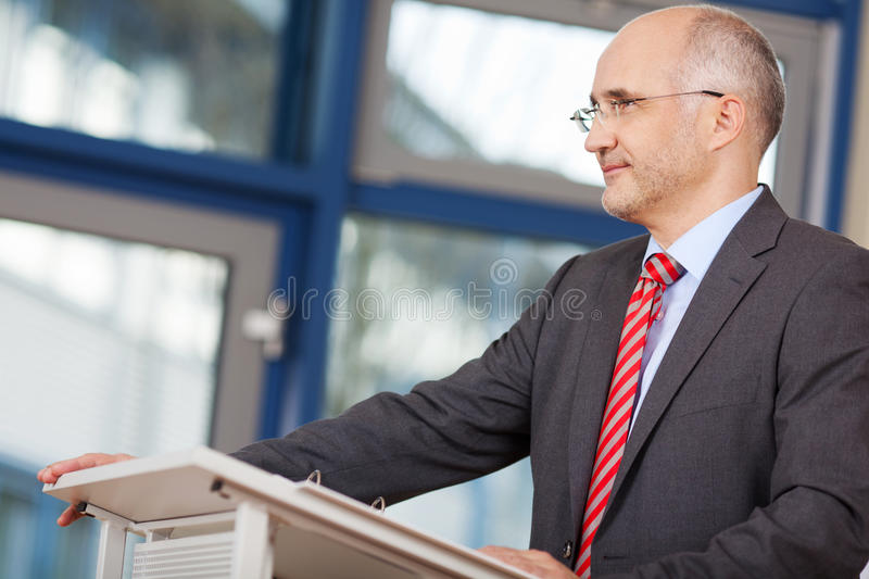 Businessman Looking Away While Standing At Podium. Confident mature businessman looking away while standing at podium in office royalty free stock photos