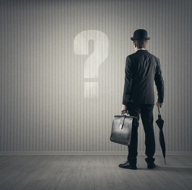 Businessman and questions. Businessman looking at big question mark royalty free stock photography
