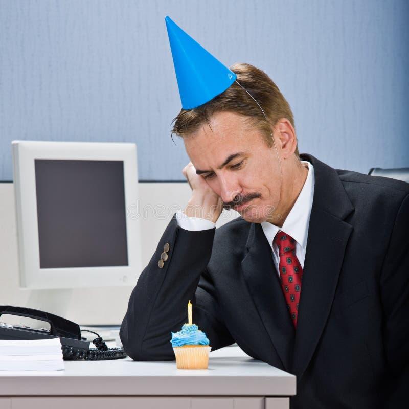 Businessman looking at birthday cupcake stock image
