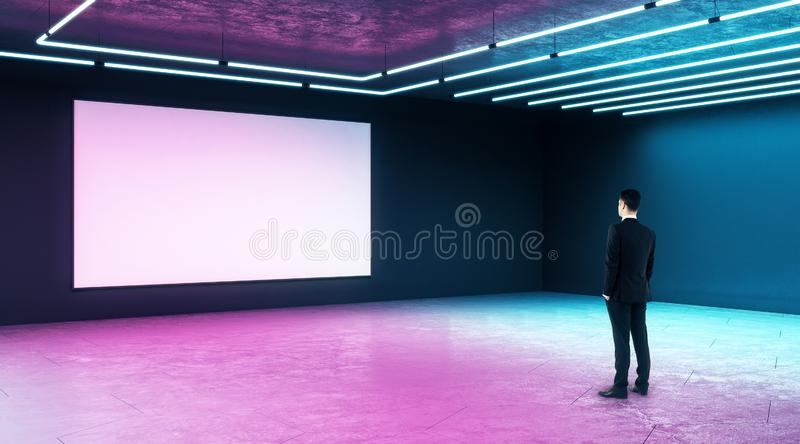 Businessman looking at white mock up poster on dark wall in modern empty hall with neon paints stock photography