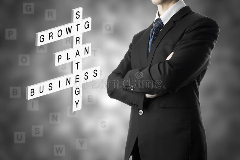 Businessman looking business concept by crossword stock photo