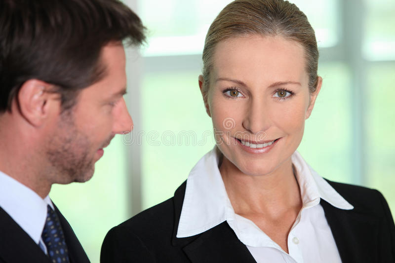 Businessman looking at businesswoman stock photography