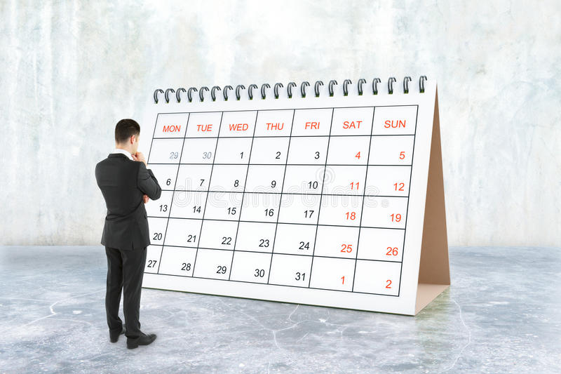 Businessman looking at calendar. Thoughtful young businessman looking at calendar placed on concrete surface. Schedule concept. 3D Rendering stock images