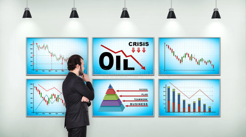 Businessman looking on chart of falling oil prices stock images