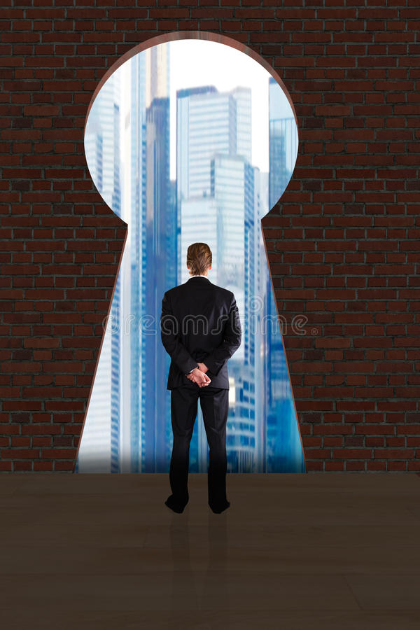 Businessman Looking At City Buildings Through Key Hole royalty free stock image