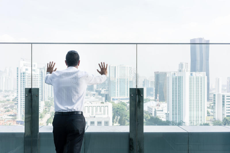Businessman looking at the city view from the top of a building stock photos