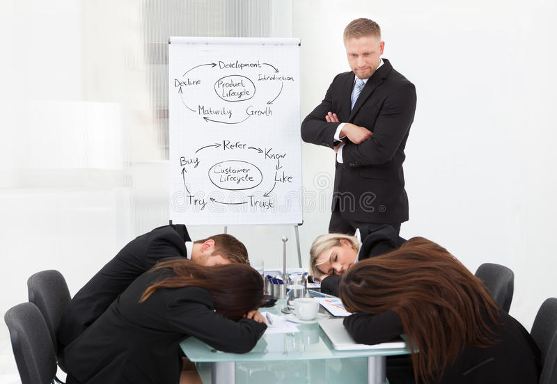 Businessman looking at colleagues sleeping during presentation. Angry businessman looking at tired colleagues sleeping during presentation in office stock images