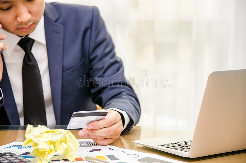 Businessman looking at the credit card in stress. Calculator accounting costs, charges, taxes and mortgage for paying bills stock images