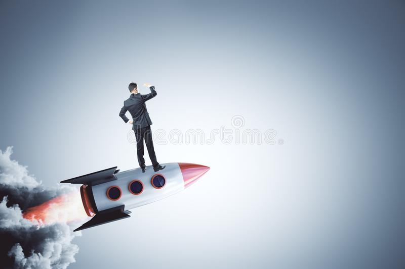 Startup and new business concept. Businessman looking into the distance on abstract launching rocket on gray background. Startup and new business concept. 3D stock images
