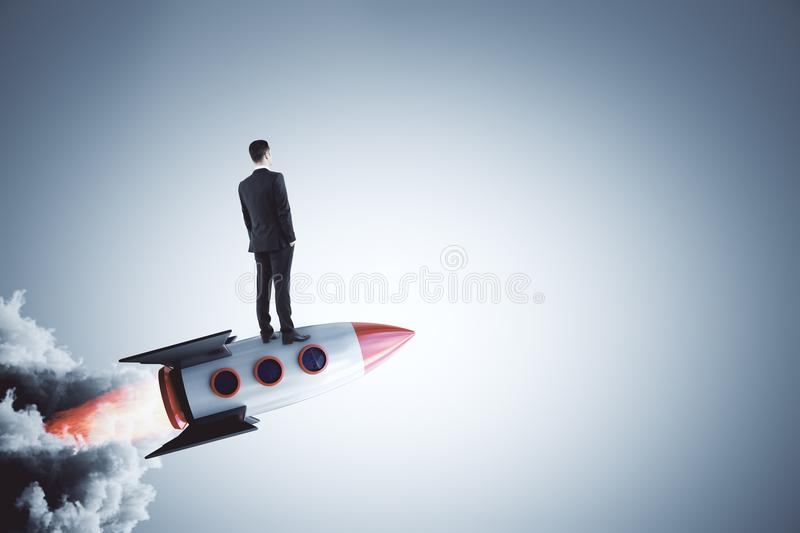 Startup and research concept. Businessman looking into the distance on abstract launching rocket on gray background. Startup and research concept. 3D Rendering royalty free stock image