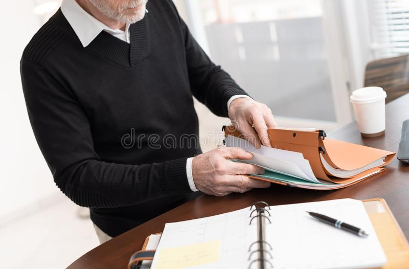 Businessman looking for document in folder stock image