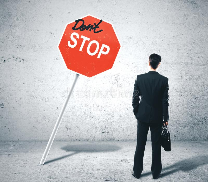Businessman looking on dont stop sign. Businessman in suit with briefcase looking on dont stop sign. Business motivation concept royalty free stock images