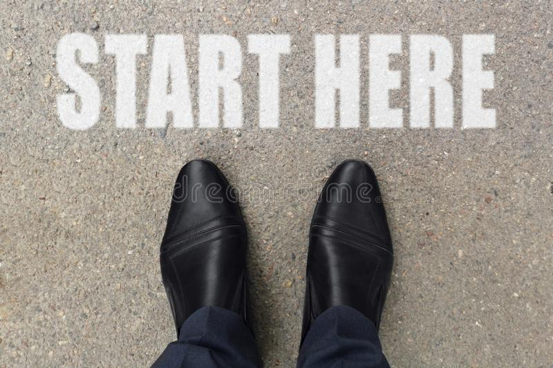 Businessman is looking down at his feet on a concrete floor with START HERE letters painted on the surface. Top view image of pers stock image