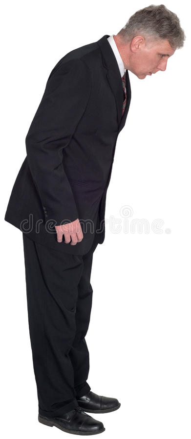 Businessman Looking Down, Standing, Isolated. A businessman wearing a suit and tie is looking down at something. Isolated on white royalty free stock photos