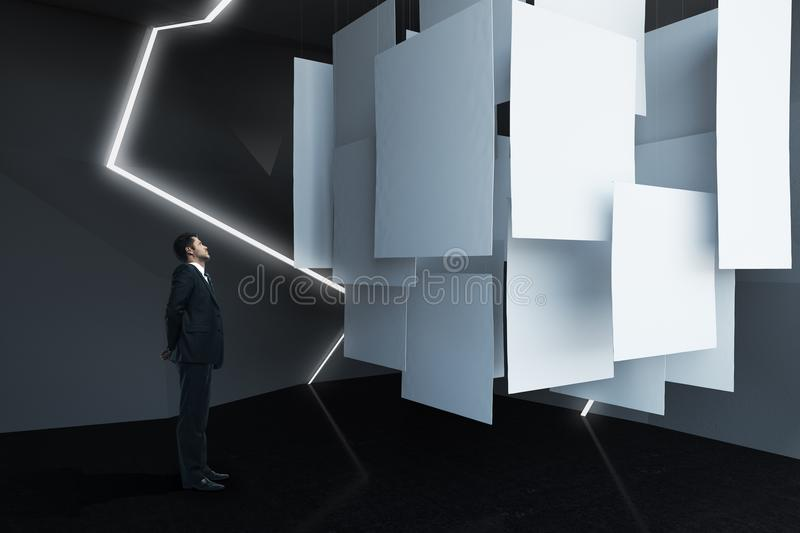 Businessman looking at banners. Businessman looking at empty banners in abstract exhibition room. Mock up, 3D Rendering stock image