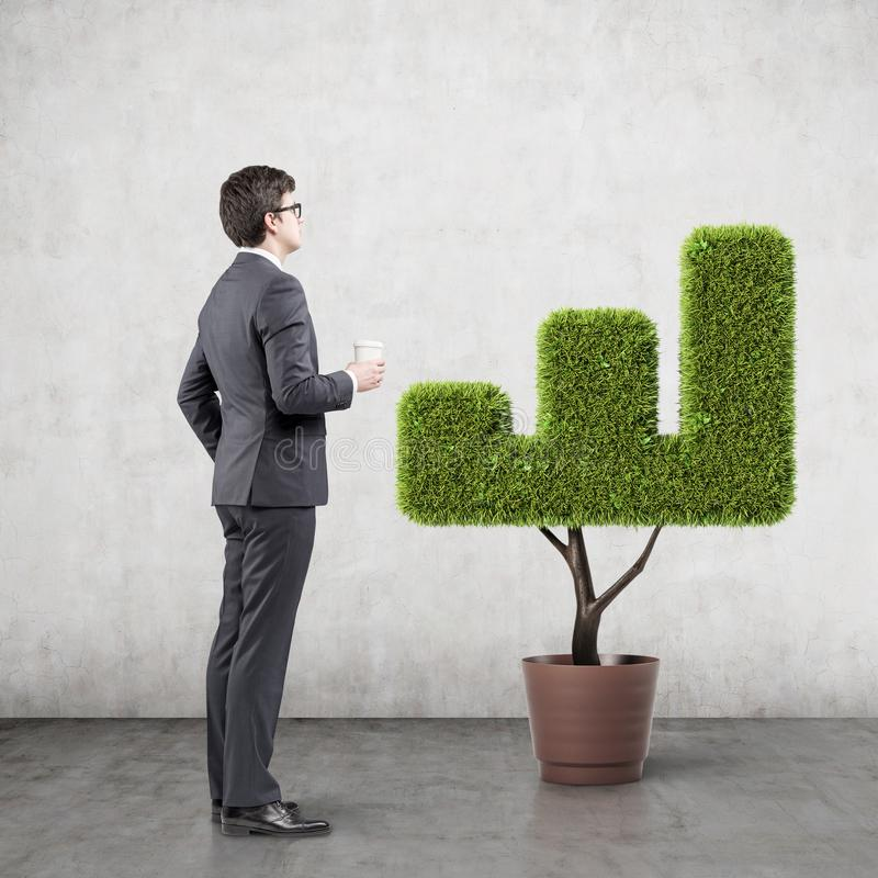 Businessman looking at graph shaped plant royalty free stock photo
