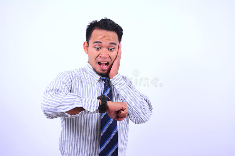Businessman looking at his watch with a surprised expression stock images