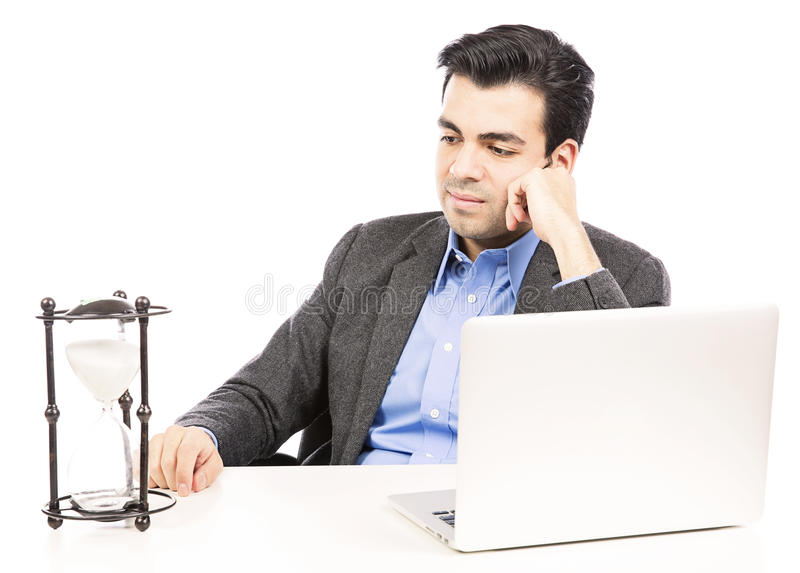 Businessman looking at the hour glass. Businessman looking at an hour glass isolated on withe background stock photo