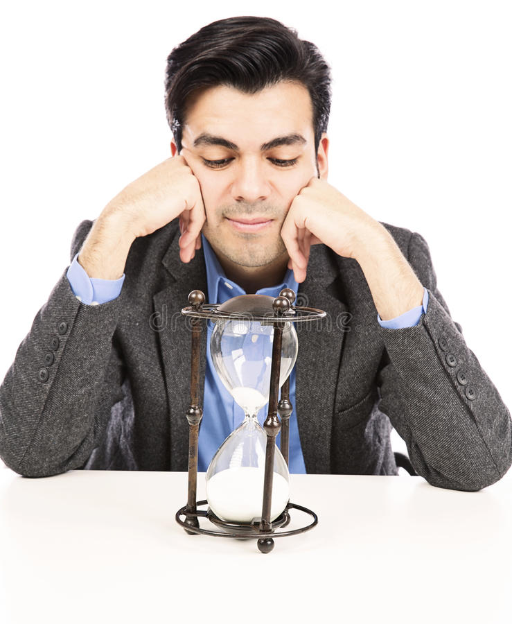 Businessman looking at the hour glass stock images