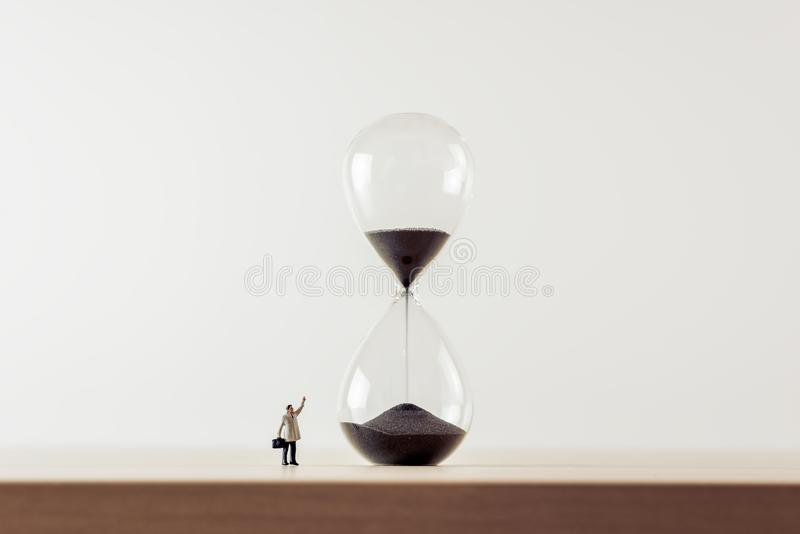 Businessman looking at hourglass. Macro photo stock photos