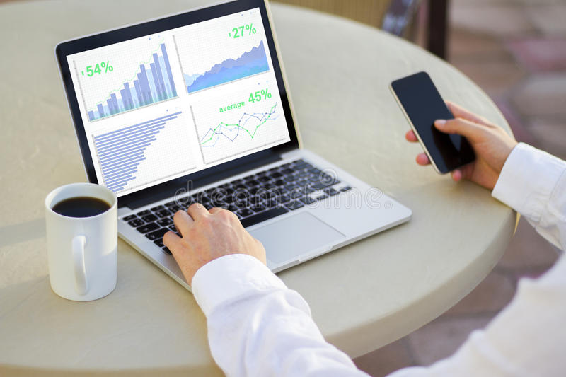 Businessman looking at laptop screen with business charts royalty free stock photos