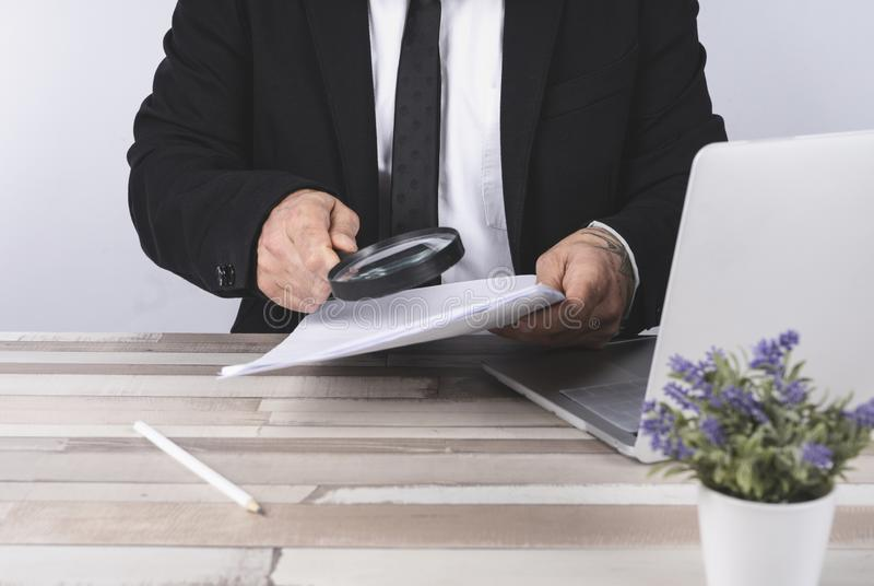 Businessman looking through a magnifying glass for documents royalty free stock images