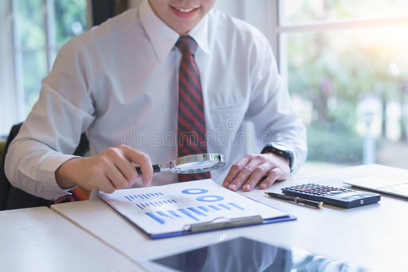 Businessman looking through a magnifying glass to business chart royalty free stock photos