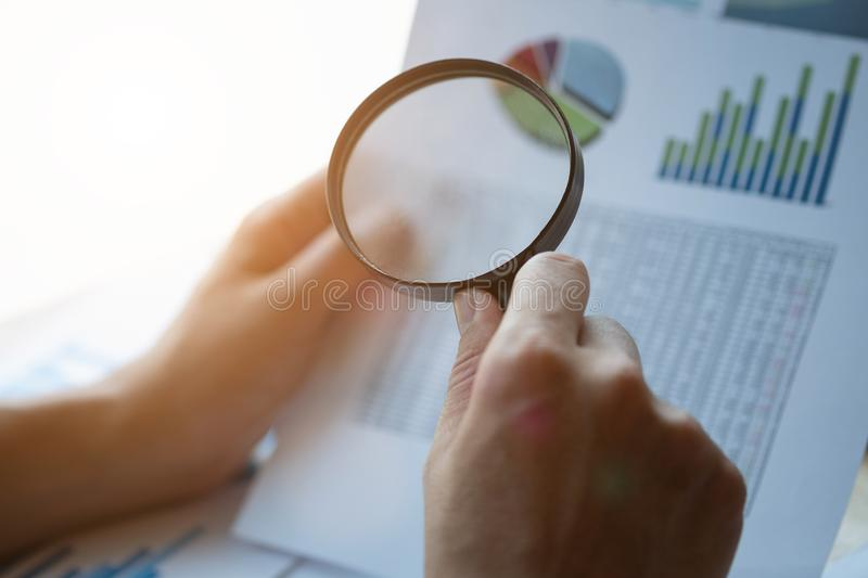 Businessman looking through a magnifying glass to documents. Business assessment and audit. Magnifying glass on a financial report. Close-up Of Businessperson stock photography