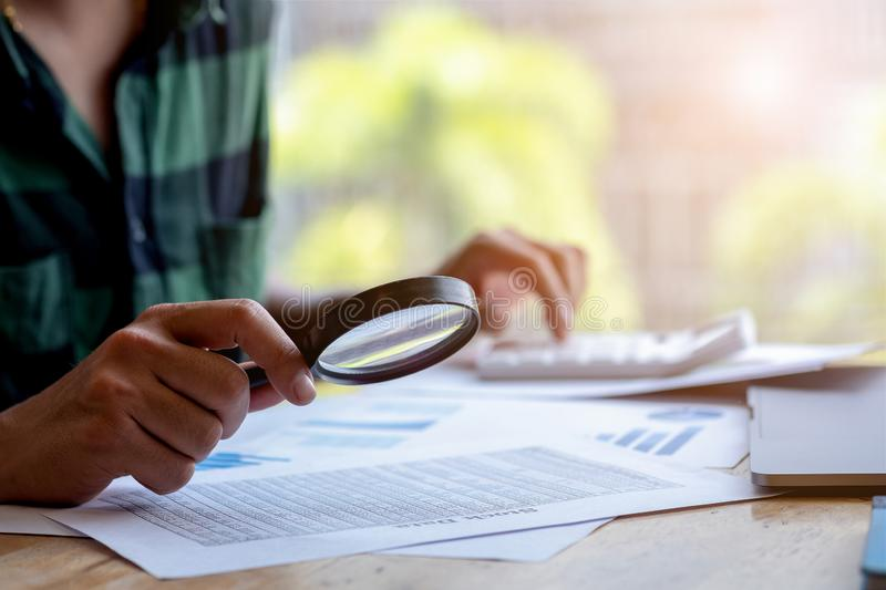 Businessman looking through a magnifying glass to documents. Business assessment and audit. Magnifying glass on a financial report. Close-up Of Businessperson stock images