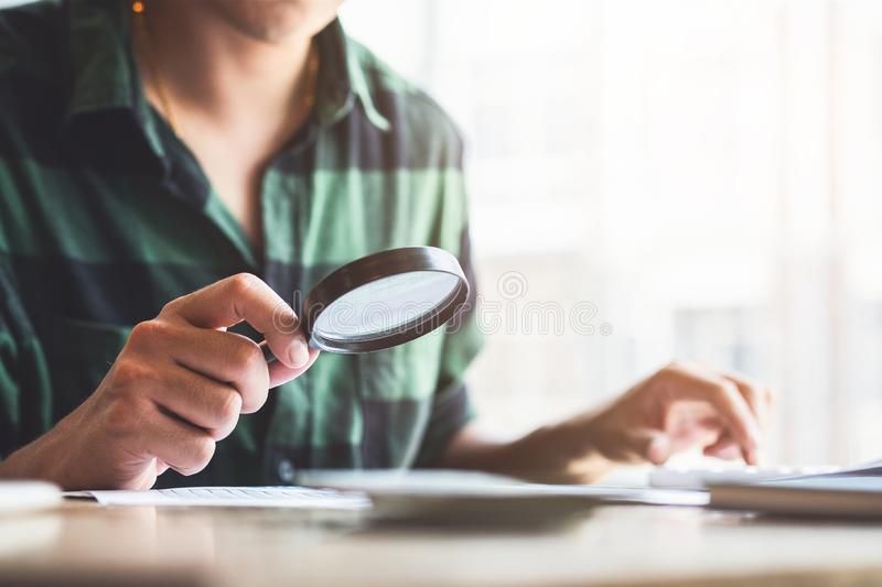 Businessman looking through a magnifying glass to documents. Business assessment and audit. Magnifying glass on a financial report. Close-up Of Businessperson royalty free stock photo