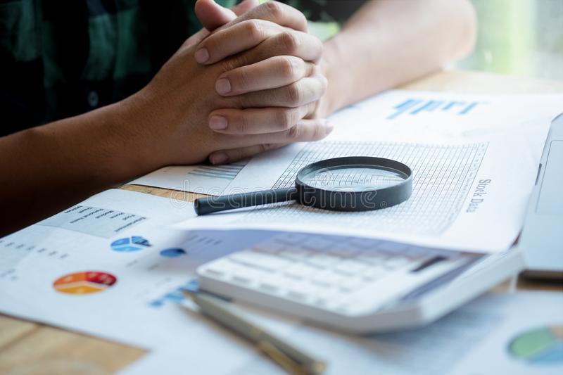 Businessman looking through a magnifying glass to documents. Business assessment and audit. Magnifying glass on a financial report. Close-up Of Businessperson royalty free stock images