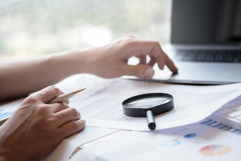 Businessman looking through a magnifying glass to documents. Business assessment and audit. Magnifying glass on a financial report. Close-up Of Businessperson stock photos