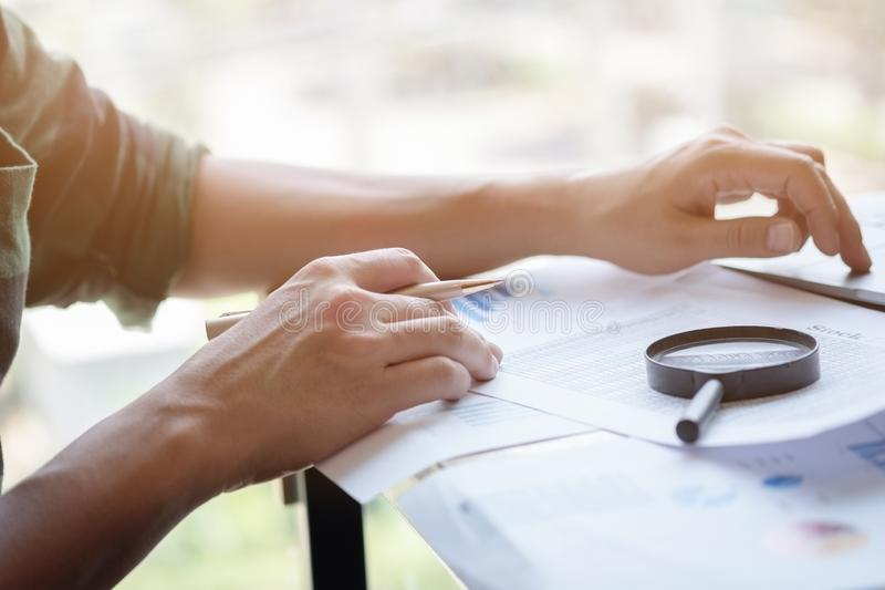 Businessman looking through a magnifying glass to documents. Business assessment and audit. Magnifying glass on a financial report. Close-up Of Businessperson stock image