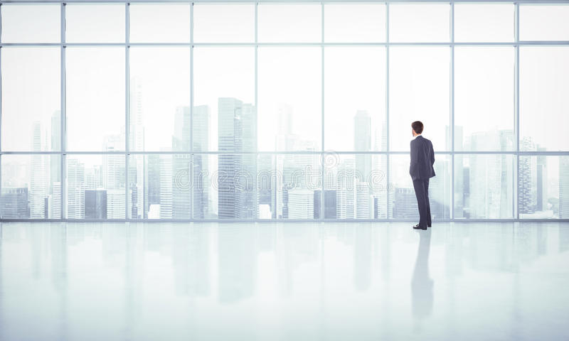Businessman looking at megalopolis through window. In the big office stock image