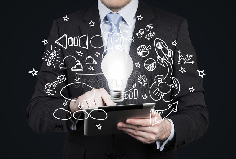Businessman is looking for new business ideas in tablet. Flying business icons and a light bulb as a concept of new idea. stock photography