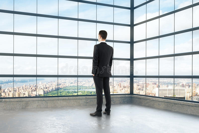 Businessman looking out the window of empty loft room royalty free stock image